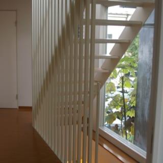 2階~3階への階段/東向きの大きな窓に面した階段。ホワイトと木目のナチュラルですっきりとしたデザインに柵状の白いアイアンを組み合わせると、スタイリッシュなアートのような存在感がある。ステップの間を空けたオープンタイプなので見通しがよく、ここから入る光を邸内全体に届けられる