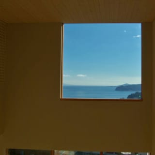 読書コーナーから吹き抜けの窓を臨む。リビングからの眺めとはまた違った海が見られる