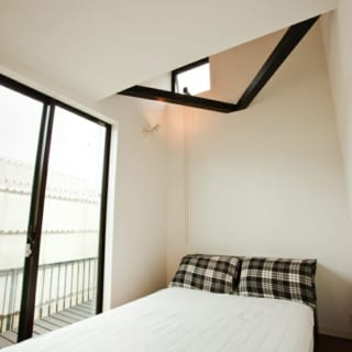 4.5畳のベッドルーム。横になったとき真上に広がる吹き抜けが開放感を演出。スレンダーな梁がアクセントを添える吹き抜け上部には、通風と採光を兼ねたオーニング窓を設けた