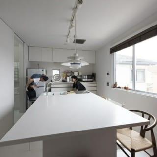ダイニングテーブル一体型のキッチン。テーブル側からシンクの方まで、一枚の板でつくったかのような仕上がり。