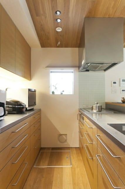 キッチン/玄関から入ってすぐのナラ材で仕上げられたキッチンもオーダーでつくったもの。調理台の前には高さのある物置きスペースを設け、リビング・ダイニングから調理中の手もとが見えないようにした