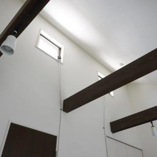空間のアクセントになっている焦げ茶色の梁は、手の届く位置に照明をつけて、メンテナンスしやすくするという意図も