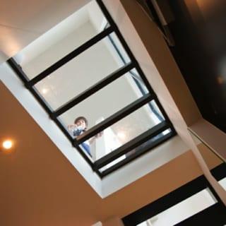 """玄関の天井部分は透明の板を通して真上のリビングから明るい光が降り注ぐ。""""透明床""""という床面積をムダにしないため手法。材質は高強度のポリカーボネイトだから上を歩いても壊れない"""