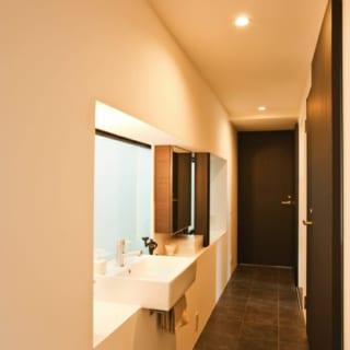 玄関から奥の寝室へとのびる廊下。床はマット感のある黒タイルで意匠性を高めた。左側の出窓には洗面台を設け、廊下兼洗面スペースに。狭小住宅ならではのアイデア