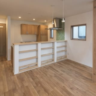 キッチンとの間仕切りカウンターには、ご夫人のアイデアで棚板の高さを変えられる収納スペースをしつらえた。日常のちょっとした小物が片付く。