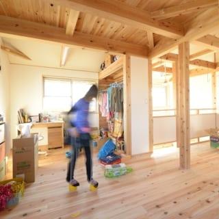 リビングの床はスギの無垢材。中央の掘り座卓は多彩な利用法が可能。大きな窓に加え、天井から明かりが入る工夫も