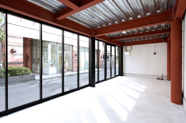 1階のテナント。床・壁の白を基調に、柱・梁の赤、サッシの黒、天井のシルバーがシンプルかつ美しく調和