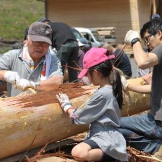 丸太の皮をむくイベントに、施主様も家族で参加。桧や杉の皮は簡単に竹ベラでむけるので、子どもでも楽しめる