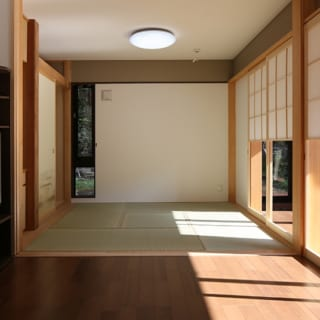 1階 座敷/茶の間側から座敷を見る。こちらも縦長の窓で視線に奥行きを与えている。窓で壁を長方形に切り離すことによってデザイン的にもメリハリが出ている。縁側との間仕切りに猫間障子が用いられ、茶の間や座敷への採光を調整することもできる