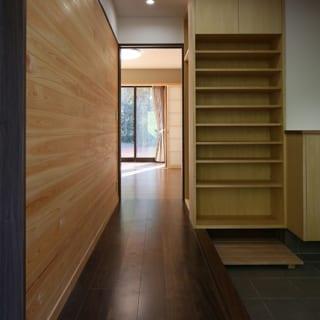 1階 玄関/画像右側が玄関扉。奥には茶の間が見える。画像左側の壁は白木のヒノキ材を使用。玄関の演出用として板壁上辺にピクチャーレールが仕込まれている