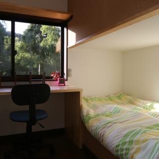 2階 子供部屋/大きなひと部屋に二段ベッドを置くこともできるが、お子さんの性別が異なるため2部屋に分けた。間仕切り壁は断面をS字状にしてベッドを配置。画像右、ベッド上部の壁の向こうは隣の子供部屋のベッドがある。お子さんの巣立った後は間仕切りとベッドはなくせるようあらかじめ配慮した