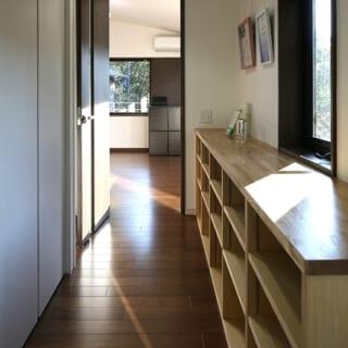 2階 廊下/写真の左手前左に入ると洗面があり、写真奥のリビングから通じる回遊動線の一部となっている。廊下の左右には収納や棚が設けられ、単なる廊下ではなく2階世帯の玄関的な場として演出できるようしつらえられている