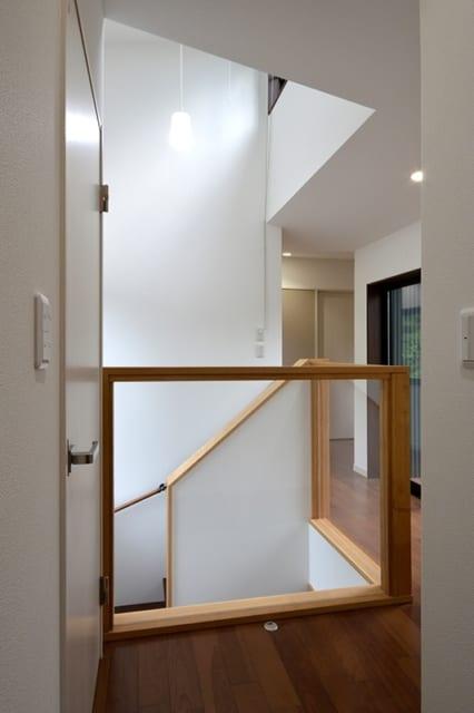 2階 階段室/階段のあるスペースは、1階から屋根まで突き抜ける吹き抜けとなっている。屋根から突き出た部分に窓が設置されており、自然光を採り入れることができる。また、陽が落ちると階段室から漏れる光を遠目に見ることができ、家路を向かうご家族の目印ともなっている