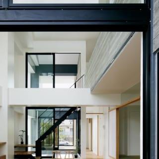 2階 南のテラス~LDK/奥の隣家側のテラスからLDKを見たところ。大きな窓やシャープな階段は視線を遮らず、南北一直線に貫かれたスキマ空間の開放感が活きている
