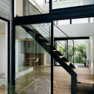 2階 北のテラス~LDK/リビングは2つのテラスに挟まれたような造り。1階の玄関から2階へ上がると1つ目のテラス。その先のリビングの奥にもテラスがあり、隣家との間にあるヤシの木を日常の景色として楽しめる。これらのテラスで隣家と距離を取っているため、大きく開口しても外部の視線が気になりにくいという効果も