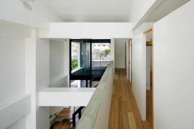 3階 廊下/開放的な吹抜けでつながる2階と3階。個室の壁の上部の欄間はガラスがはめ込まれており、室内からの視線が行き止まりにならず空間を広く感じられる。夜は明かりが漏れて気配がわかり、家族の一体感がより高まる。このガラスの欄間は2階の畳の小上がりにも用いられている