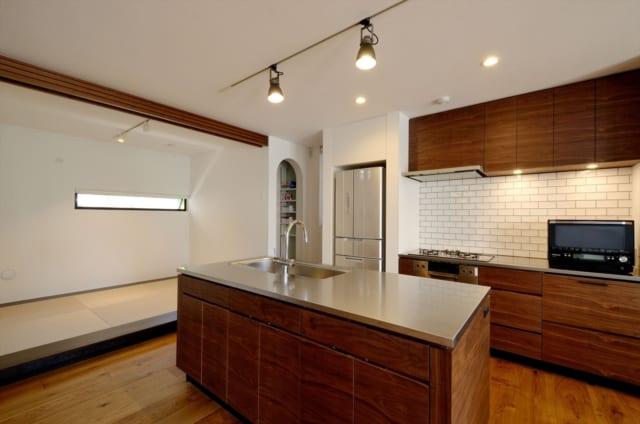 1階 キッチン/回遊できるアイランド型キッチンの周囲には、パントリーと畳の小上がりスペース。小上がりはブラインドを下ろすと客間に早変わり