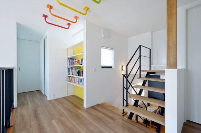 2階 ホール/2階のホールでは、レインボーカラーの雲梯がお出迎え。本棚もあり、遊びのスペースとなっている。階段を登った先には収納庫として使えるロフトも