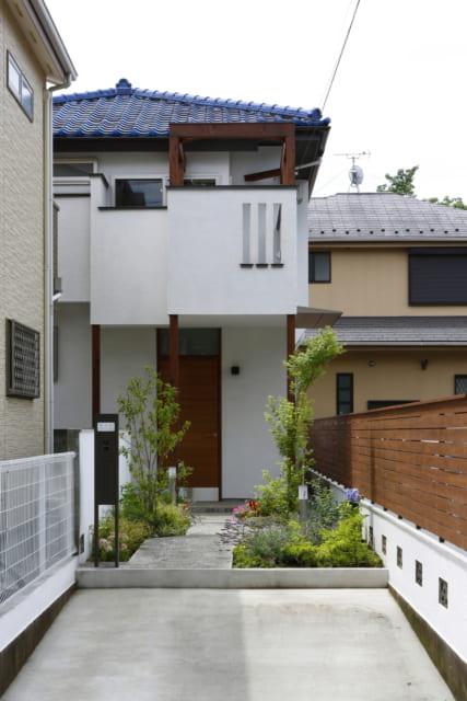 外観 玄関/青い屋根はそのままに、新たにバルコニーを設置。ウッドフェンスでナチュラル感を演出。アプローチのゆるやかなカーブが、植栽の小道を通る楽しさをもたらす