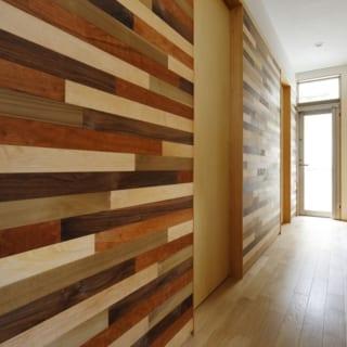 1階 廊下/様々な色の木を使ったモザイク模様が、寄木細工を思わせる落ち着きを与える。居室のドアを引き戸にすることで、和の雰囲気も