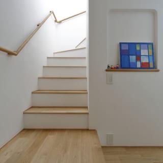 1階 階段付近/階段上からの光が漆喰の白壁を優しく照らす。壁に設けられたニッチには、四季折々の絵画などが飾られ、季節感が演出されるという