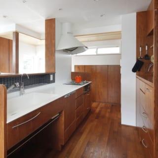 2階 キッチン/奥の壁にも収納を設けるなど、使い勝手の良いキッチン。背面の棚は奥様の背丈に合わせ高さを調整。奥様のこだわりだという白い換気扇フードがかわいらしい