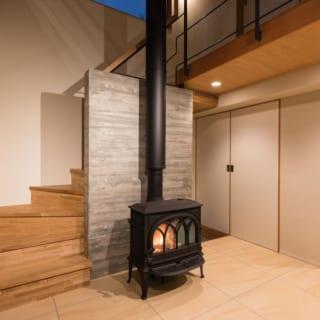 1階 薪ストーブ/暖められた空気が吹き抜けを通って2階に上がるため、1階も2階も温かい。使用する薪は、隣の林から出た木材をOさん自らが薪にしている