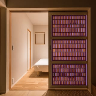 1階 ベッドルーム/1階にあるベッドルームのドアも、アクリルの組子細工。外の光が差し込むと、床に美しい模様の影を落とす