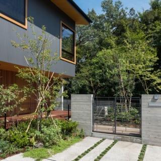 アプローチ/コンクリートにスリットを入れたアプローチ。門扉には鉄を使った格子を使用しており、鉄でありながら重くなりすぎない繊細なデザインとなっている