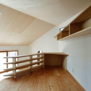 寝室/建物の一番奥にある寝室。棚や机を造り付け、書斎のように使えるようにした機能的な空間だ。リビングの、庭に面した壁に向かって天井が低くなっているのがよくわかる
