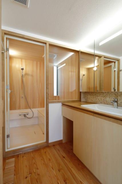洗面所・浴室/浴室はヒノキを貼ったハーフユニットバス。ひとりで暮らすために十分な機能性を持った浴室はヒノキの香りで豊かさもうまれ、ほっとする空間に。お母様のご希望で洗面台のシンクは大きいものを選んだ。床の、すのこ状になった部分は床下空調による空気の出入り口。ヒートショックなどの不安も軽減されるだろう