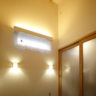 2階 寝室/高さをとることで、空間の広さを演出。壁からの壁付照明が枕元を照らす