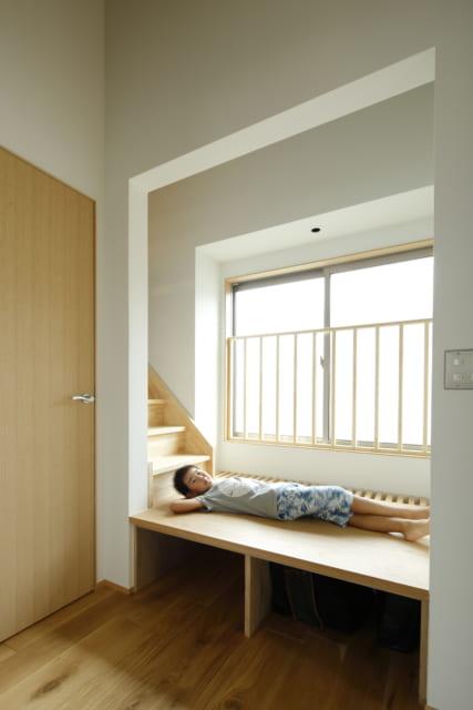 2・3階 階段/ロフトへと続く階段の1段目は、ちょっとした小上がりスペース。下部が収納となっている他、奥が格子状になっており、1階への採光と通風の役割を担う
