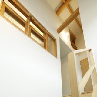 1・2階 階段/洗面室との壁には窓が設けられ、換気と南面の窓からの光を取り入れる役割を担う