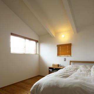 2階 主寝室/張り出した屋根の下にあたる。白でまとめられた空間は広がりを感じられ、天井が低めの部分も斜め天井で圧迫感がなく、かえって落ち着く部屋となっている