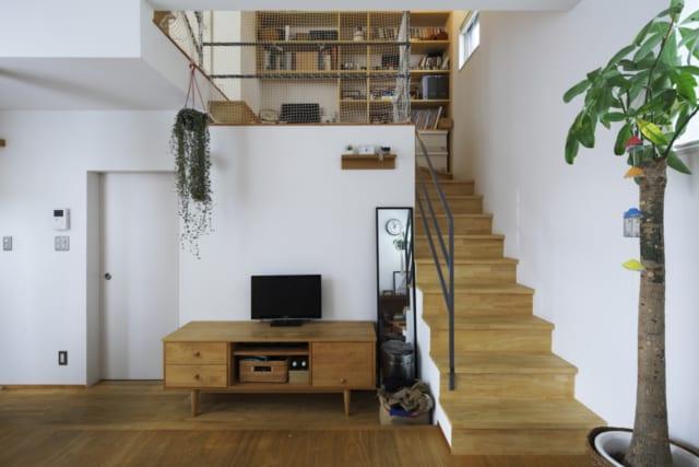 1階 リビング/階段の上は中2階。その先をもう一段あがると2階の居室がある。テレビを見ながら中2階で遊ぶ子供たちを見守ることもできる。左の扉はファミリークローゼットに通じている