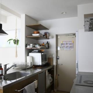 1階 キッチン/オーダーメイドのキッチン。デザインもさることながら、使い勝手もカスタマイズされている。シンクはリビングに、ガス台は壁に面している。洗い物をしながらテレビや中2階を見渡すことができるし、火の回りは汚れにくく、安全な配置はうれしい