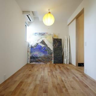 奥さまが描いた絵画を飾った1階の洋室。将来的に2つの子供部屋に区切れるように入口を二つ設置している。