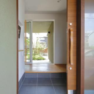 「日本的な暮らし方が一番快適だと思うようになった」ことから、玄関扉は引き戸に。目線の先には中庭があり、家に入るなり癒される。