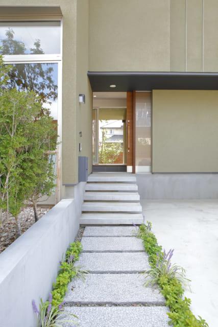 玄関までのアプローチは緩やかな階段で奥行き感を演出。前庭の風景も印象的だ。