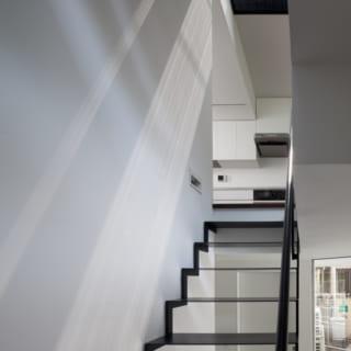 玄関ホールからの見上げ。2階のキッチンと、3階のテラスに対しての広がりが感じ取られます。玄関ホールは、駐車場と上部への二つの方向への広がりを持つ空間です