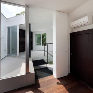 3階は、中庭と一体となったワンルームのスペースです。ちょっとした段差や、引き戸、床仕上げの違いで、各々のスペースを性格づけています。手前は寝室。引き戸で階段に対して、仕切られます。右手は床のフローリングと同じような色で仕上げた収納の扉