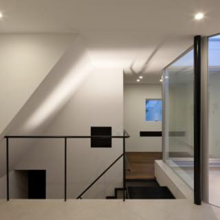 寝室から40センチ上がったスペースは、書斎。書斎とテラスは一体のスペースとして、タイル(1階と同じ物)で仕上げました。 左手の窓は、折れ曲がった屋根の上に出来た空地に対する窓。「外への開口部」と「黒の開口部」がよく見えるアングル