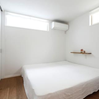 シンプルで落ち着ける1階の寝室。大きな窓はないが、上方にもうけられた窓で明るさを確保している