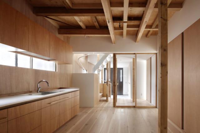 1階のキッチンのカウンターや棚は造作で作られたもの。素材はラワン材や杉など限定することで統一感を出した