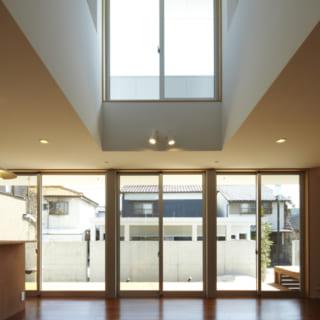 1階からみた吹き抜け/2階に設けられた採光用の窓。1階リビングから見上げたとき気持ちの良い空が見える。