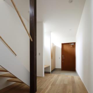 Nさま自邸の玄関ホール。板状の階段は軽やかですっきりとした印象。玄関の奥から中庭を通して母屋にアクセスできる。