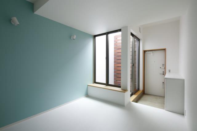 賃貸部分のリビングルームは玄関一体型。限られた面積を有効活用している。窓と木製ルーバーの間に光庭を設け、実際の面積以上の開放感を創造している。