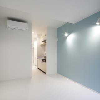 賃貸部分はワンルーム設計ながら、部屋の中央部に水まわりをまとめているため寝室とリビングがゆるやかに分離。廊下とキッチンスペースを共有することでスペースも有効利用。