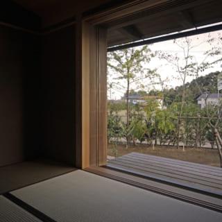 夫婦の寝室となっている和室では、大きく窓を開放して外を感じることができる。杉の木枠を用いた照明はFさんが京都から見つけてきたもの